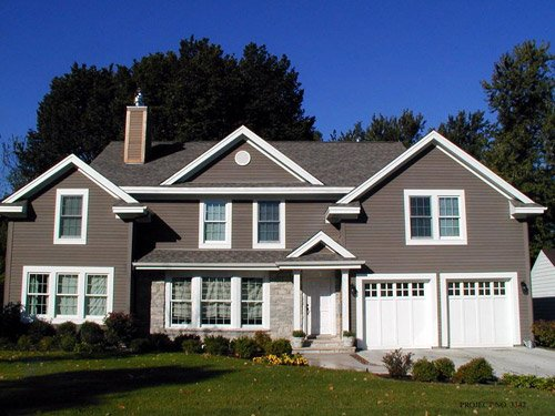 huge house with white garage door and gray sidings