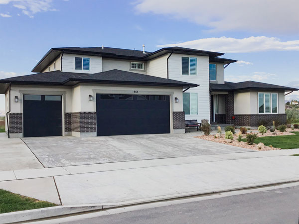 huge house with white sidings and blue garage doors