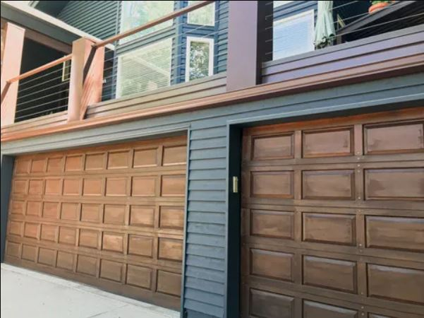 two brown garage doors and balcony railings above